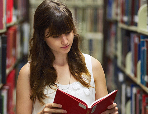 Female Student reading book in library